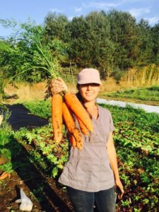 Good Farm Fund grant recipient Isa Quiroz shows off some of Tequio Community Farm's first season of carrots farmed using biointensive and sustainable methods on leased land at Ridgewood Ranch.
